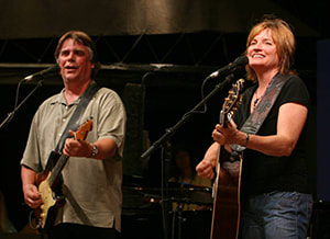 A man and woman stand on a stage with guitars. Photo Credit: Archbold Music Commission