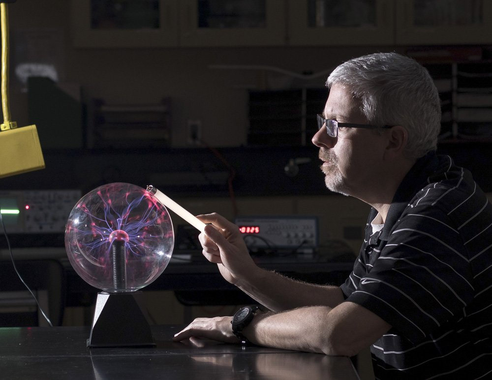 A man in a striped polo shirt sits in a dark room holding a light bar to an orb of electricity. Photo Credit: Jeffery S. Hall photography
