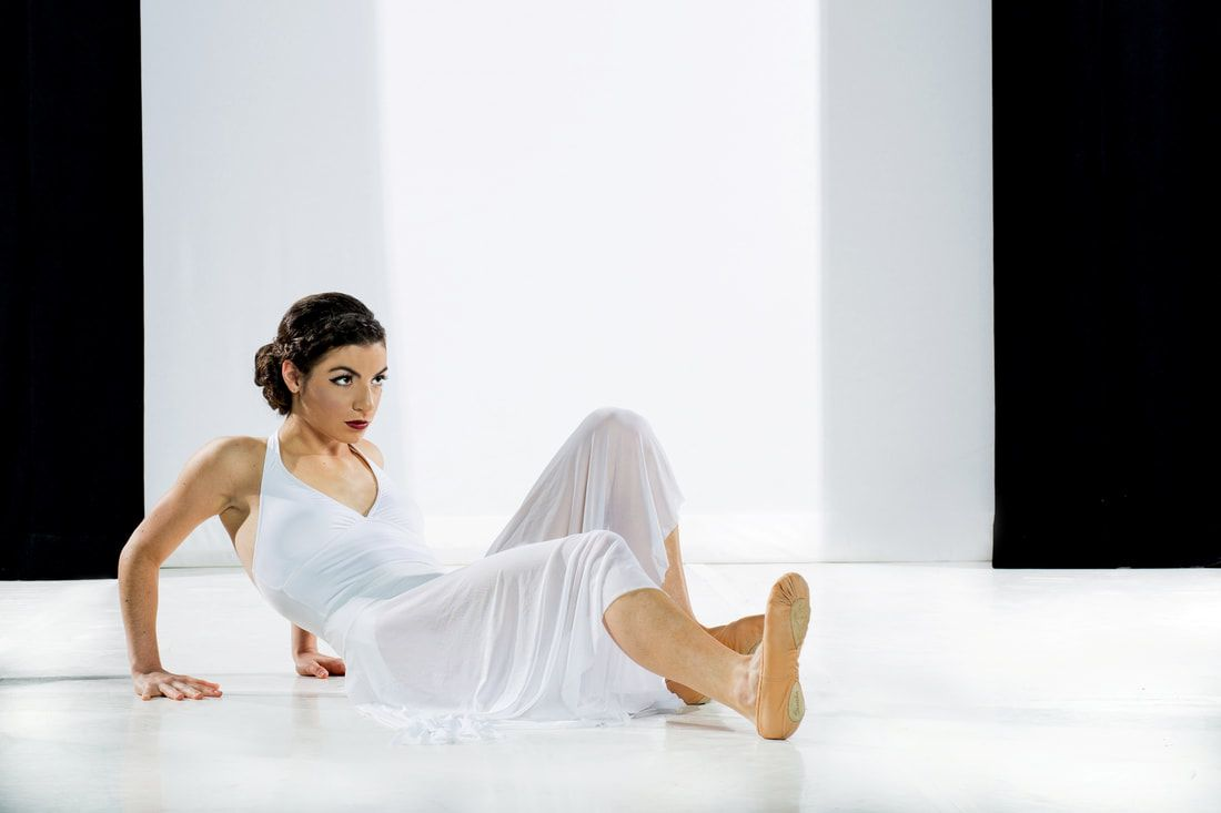 A woman dressed in white lies on a white stage with one leg extended in front of her. Photo Credit: Zaire Kacz
